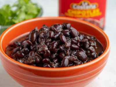 Cooked black beans in an orange bowl with a jar of chipotles behind it