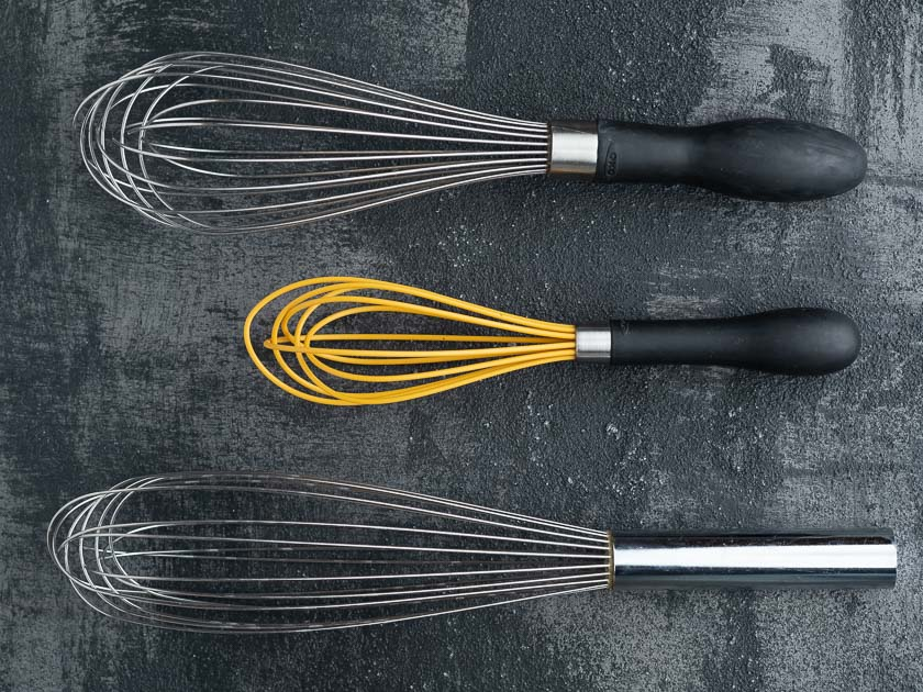 A balloon whisk, a mini-whisk, and a french whisk on a black background