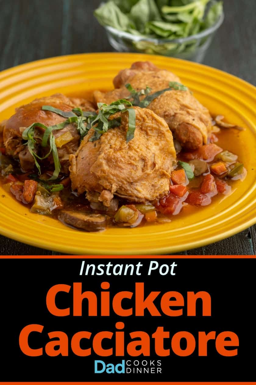 Chicken cacciatore: Chicken thighs, sprinkled with basil, on a bed of cooked vegetables and cooking liquid, on a yellow plate, with a bowl of basil in the background.
