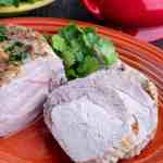 A sliced pork loin roast on an orange platter, with parsley and a gravy boat in the background