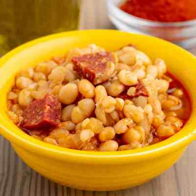 A yellow bowl of alubia blanca beans with chorizo and a red sauce, with olive oil and smoked Spanish paprika in the background.