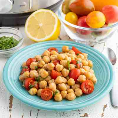 A plate of chickpeas with tomato lemon vinaigrette on a white table, with an Instant Pot, some minced basil, a half a lemon, and a bowl of tomatoes in the background.