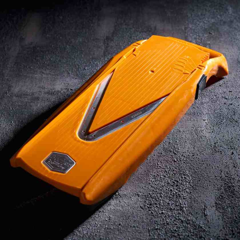 Orange mandoline on a black surface with dramatic lighting