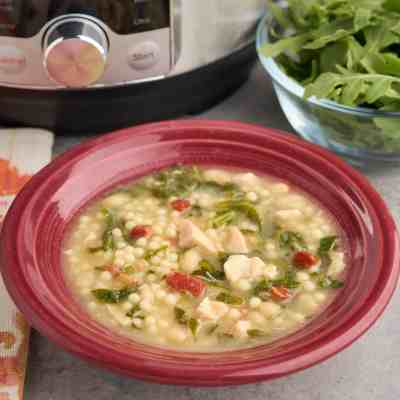 A bowl of chicken and herb soup, with bits of chicken, pancetta, herbs, and pasta visible, and an Instant Pot and bowl of arugula in the background.