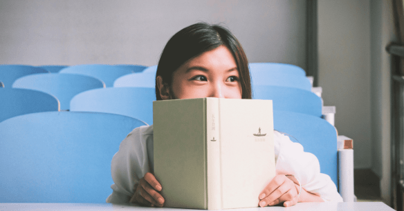 Image of a girl peeking over the top of a book in class