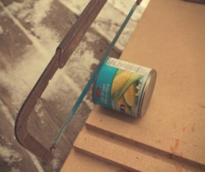 Image of a can being sawn open with a hacksaw