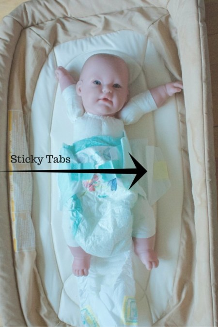 Image of a doll wearing a disposable diaper lying on a new diaper