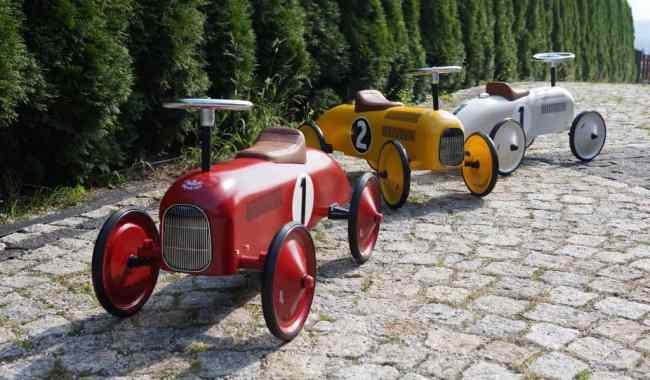 Jeździki dla dzieci, w ogrodzie. Na zdjęciu przedstawione są jeździki marki Vilac, metalowe w stylu retro, w trzech kolorach: jeździk czerwony, jeździk żółty, jeździk biały.
