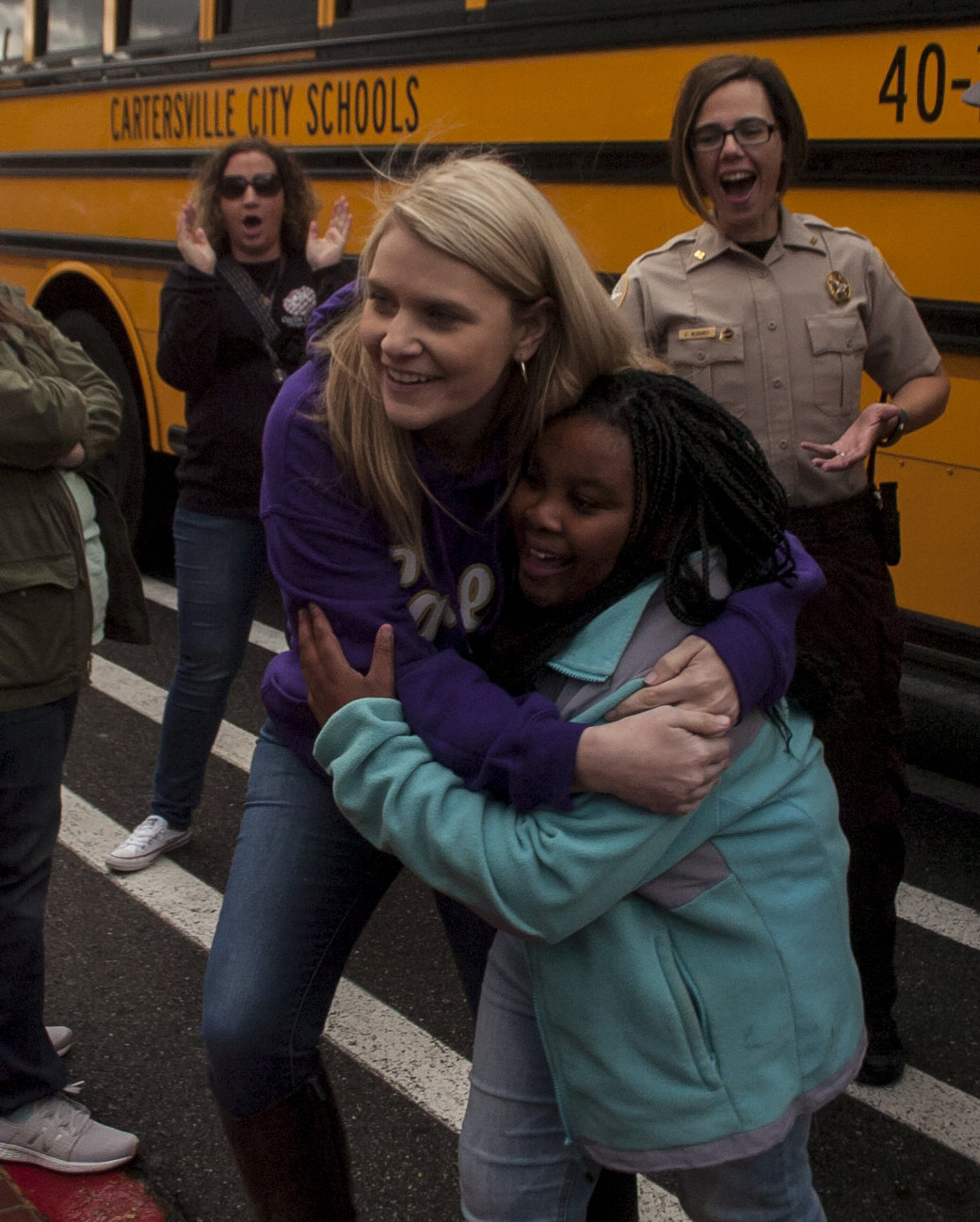 Jennifer Williams, left, hugs her designated shopper for the day, Aryannah Porter, as the two meet after Porter gets off the bus at Walmart during the Shop with a Hero event Saturday morning.