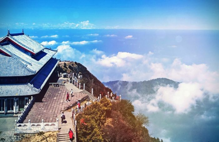 the Buddhist temple is perching on the edge of the mountain, people are walking up the staircase and on the terrace in the foreground, cloudy sky is in the distance