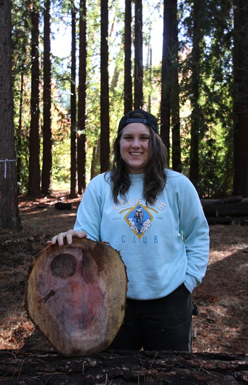 """Forestry major Madeline Green poses with a """"cookie"""" she sawed off the log."""