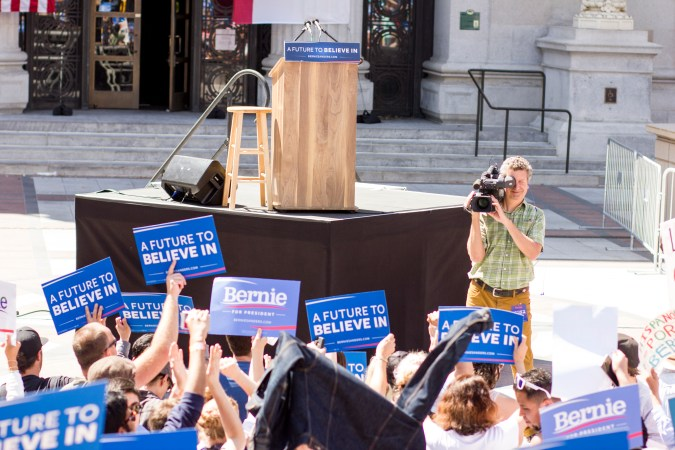 """People holding """"A future to believe in"""" signs while waiting for Bernie to appear"""