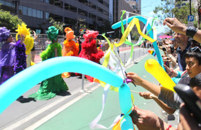 Children wave ribbon and balloons near end of parade route