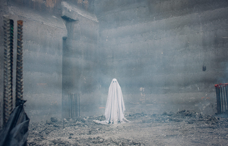 Ghost from a ghost story looms, lonely and alone, in a dark corner