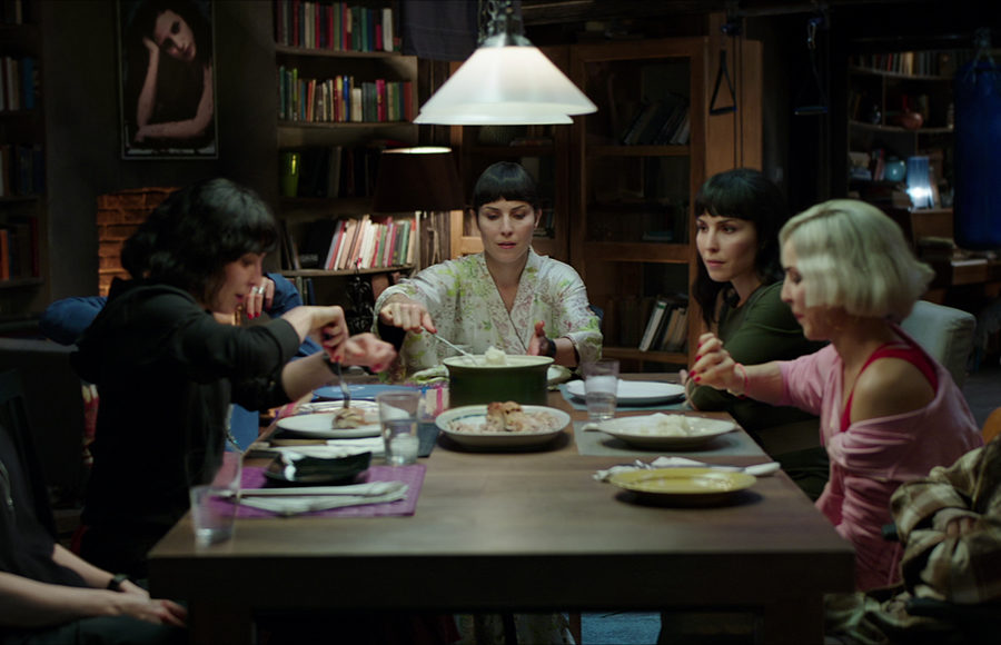 The Settman sisters (all played by Noomi Rapace) sit at the dinner table in their home.