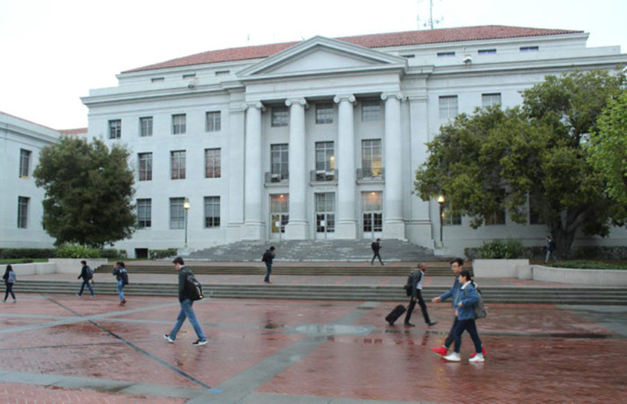 A few students walk across Sproul Hall on a gloomy day, just after the rain.