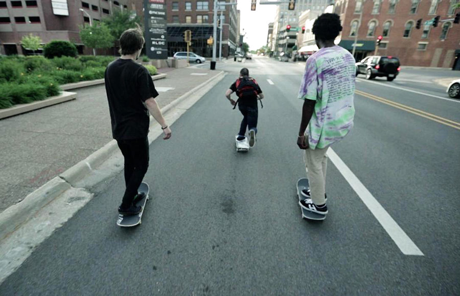 Three young men riding their skateboards through the downtown of an urban city.