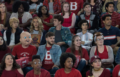 Five rows of a large audience are pictured as they all look to the right in amusement. One of the audience members has a baby mask.