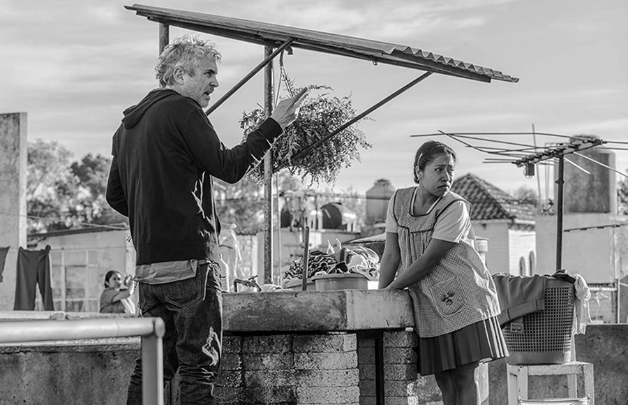 A woman and a man stand at a rooftop and look to the right as the man points.