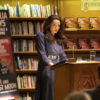 "A woman in a long blue dress and long brown hair stands behind a podium with a serious expression as she addresses an audience. A bookshelf covers the wall behind her. Next to her is a sign with the words ""Amelia Hays Book Talk & Signing""."