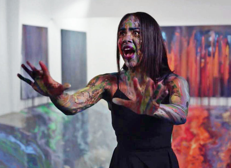 Woman covered in paint as large canvases covered in splattered paint of many colors are displayed on the walls. The woman exclaims in shock. The floor is also covered in paint.
