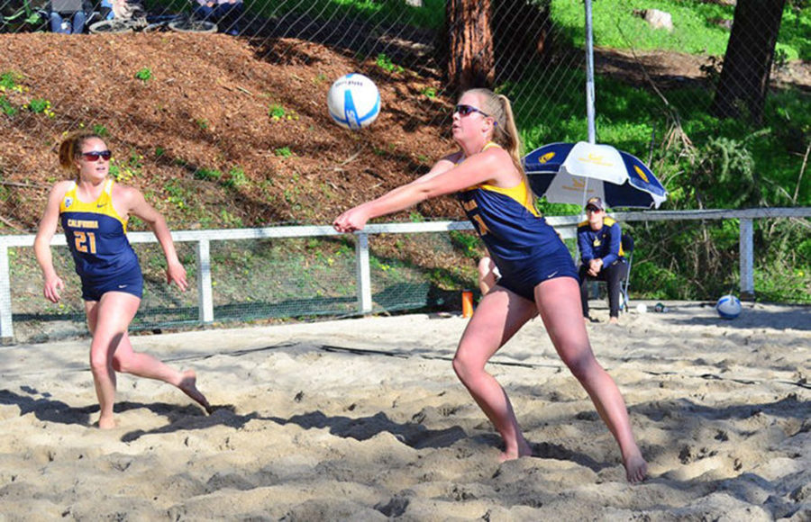 A volleyball player bumps the ball while on the sand.
