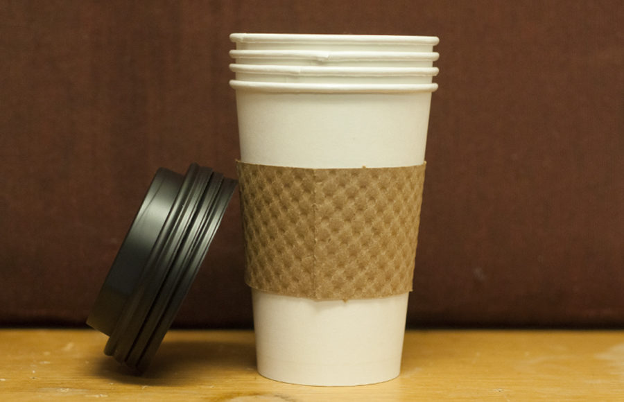 Four cups of coffee stacked inside each other as a single lid stands balanced against the cup at approximately a 45 degree angle