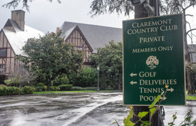 "A green sign reads ""Claremont Country Club"" in front of a brown wooden building with many trees."