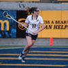 Lacrosse player runs with the ball in her stick.