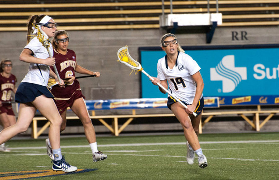 Player runs across field with ball in her lacrosse stick as other players chase after her.