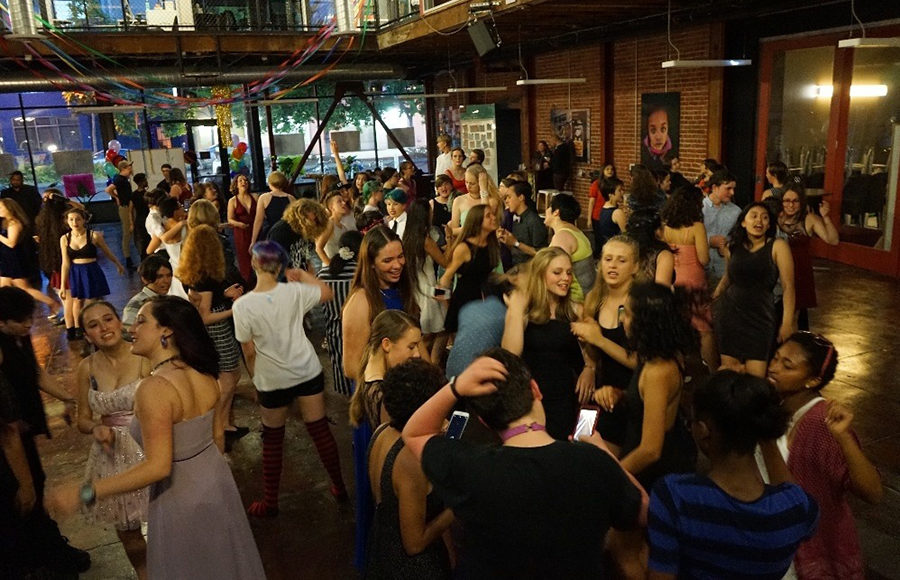 A large group of people dance inside of a building.