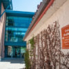 """Building with orange sign that says """"University Health Services"""" in white letters, as a building with glass windows can be seen in the background."""