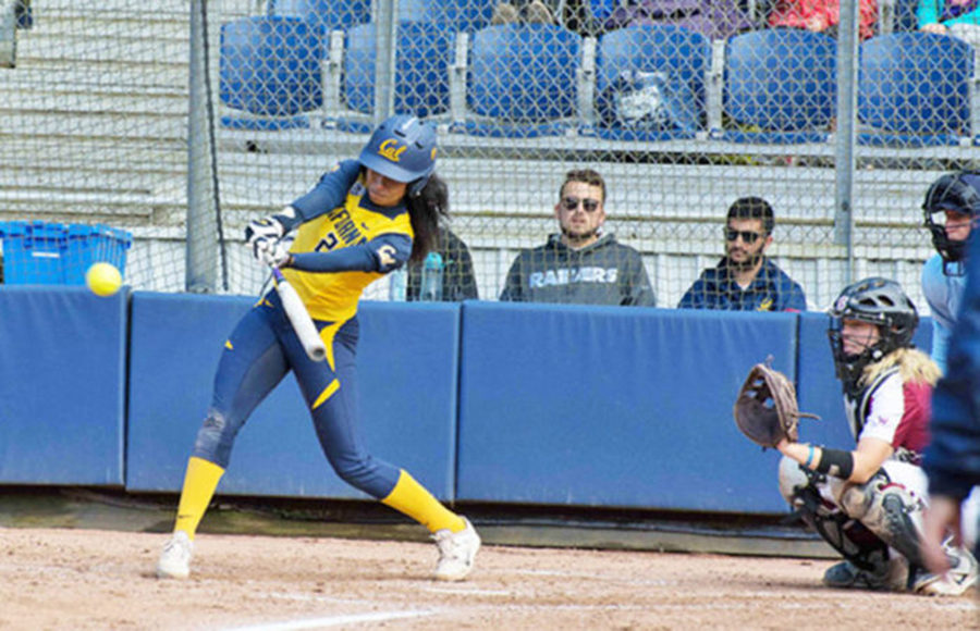 A softball player is about to strike the ball with her bat.
