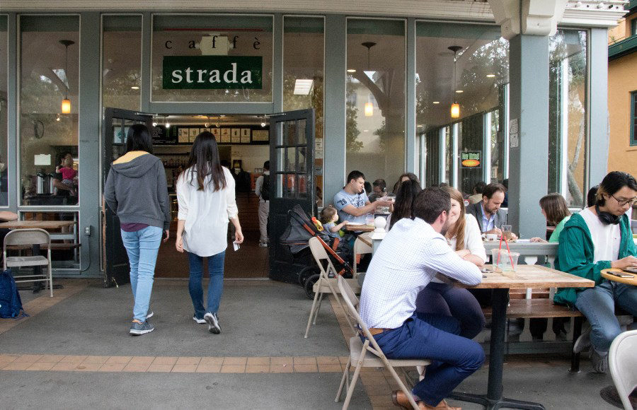 "People sit at tables outside of a cafe while engaging in conversation. The sign of the cafe is pictured saying ""cafe strada"". Two women walk in."