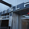 """Large metal building with the word """"TESLA"""" on it in large letters."""
