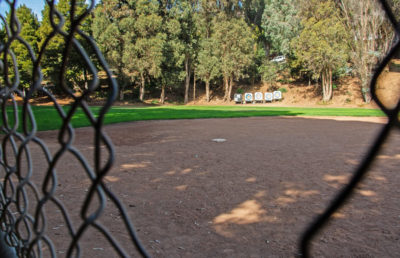A broken chain link fence gives view to an empty baseball diamond.