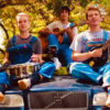 Three young men sit on a car with instruments.