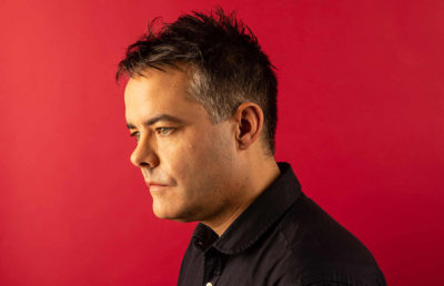 A portrait of a man looking away against a red wall.