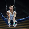 A gymnast performs in his competition while suspended in the air.