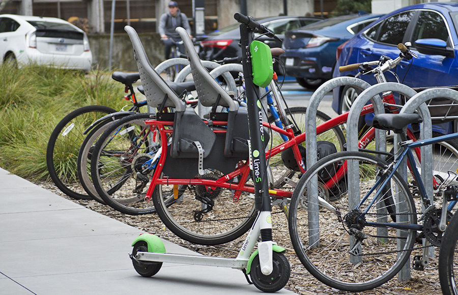 A scooter stands alone in front of a rack full of bicycles.