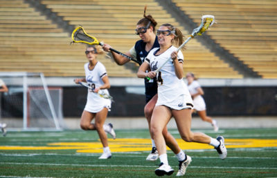 Lacrosse player runs through the field as other players chase her.