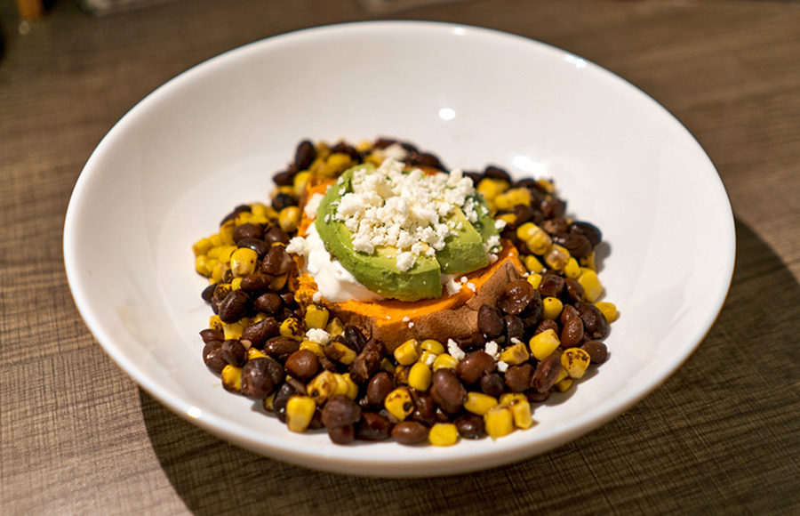 A white bowl containing beans, corn, and a sweet potato covered in sour cream, avocado, and cheese.