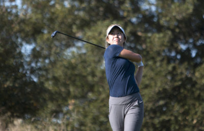 Gold player swings her club.