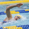 A swimmer comes up for air while swimming in a competition.