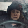 A woman sits in a car and stares at the steering wheel with an expression of dismay.
