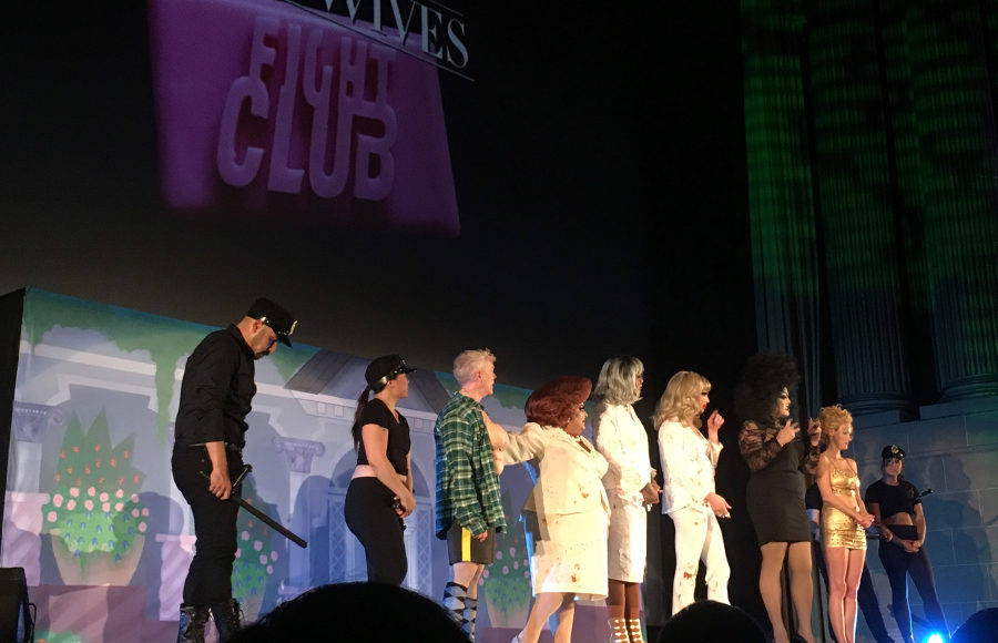A group of performers stand in a row on stage.