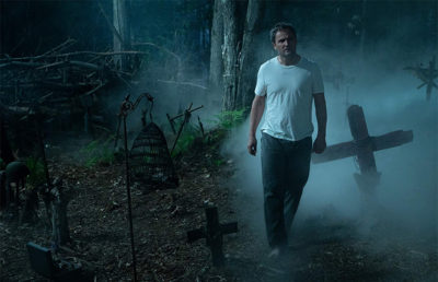 A man walks through a dark cemetery at night as fog forms behind him.