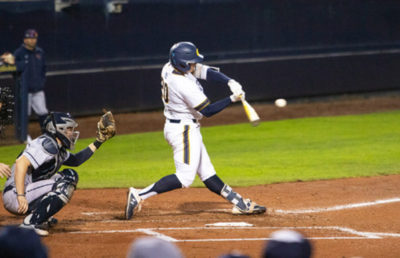 A baseball player swings at the ball with his bat.