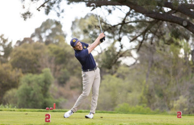 Golf player swings his club.