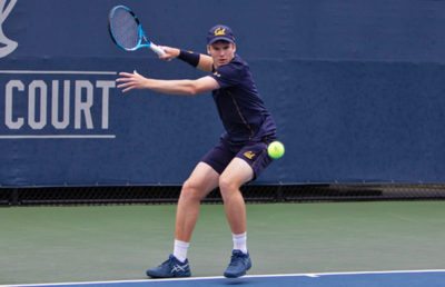 Tennis player prepares to strike the ball.
